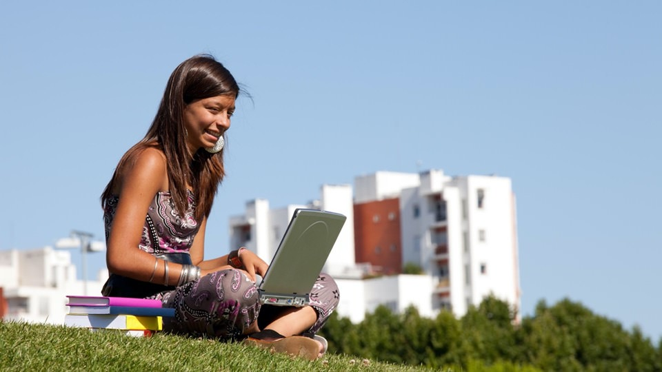 Young girl sitting outside with her laptop